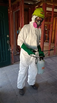 Volunteer in hazmat suit cleans house